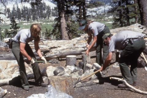 Three NPS employees clear the ground around a designated fire area on a wooded landscape