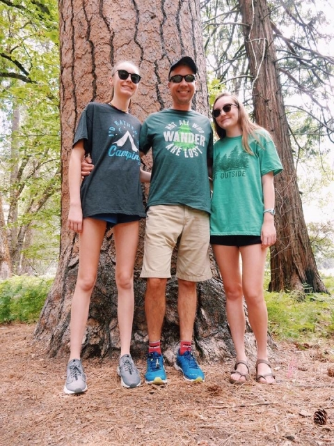 Champions Society Member Frank Hanzlik stands with his two daughters next to a tall tree in Yosemite National Park
