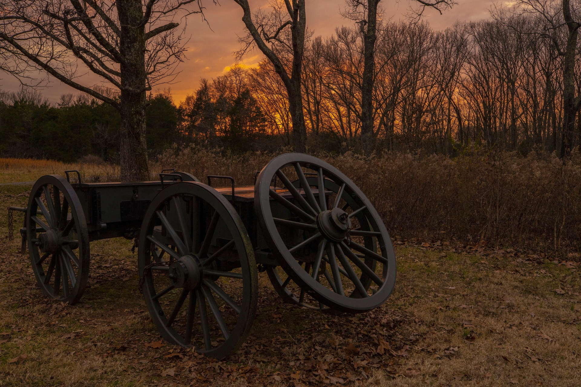 A old wagon on a battlefield at dusk