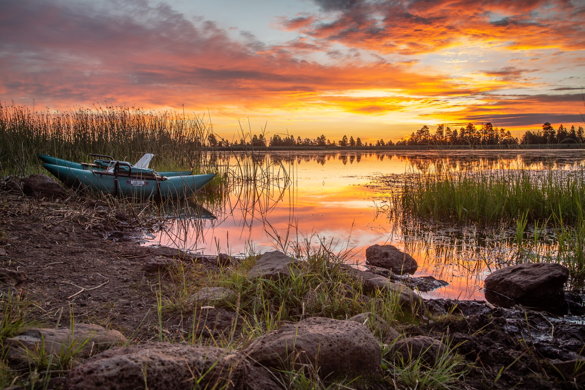 A pontoon boat on the shore of a lake at sunset