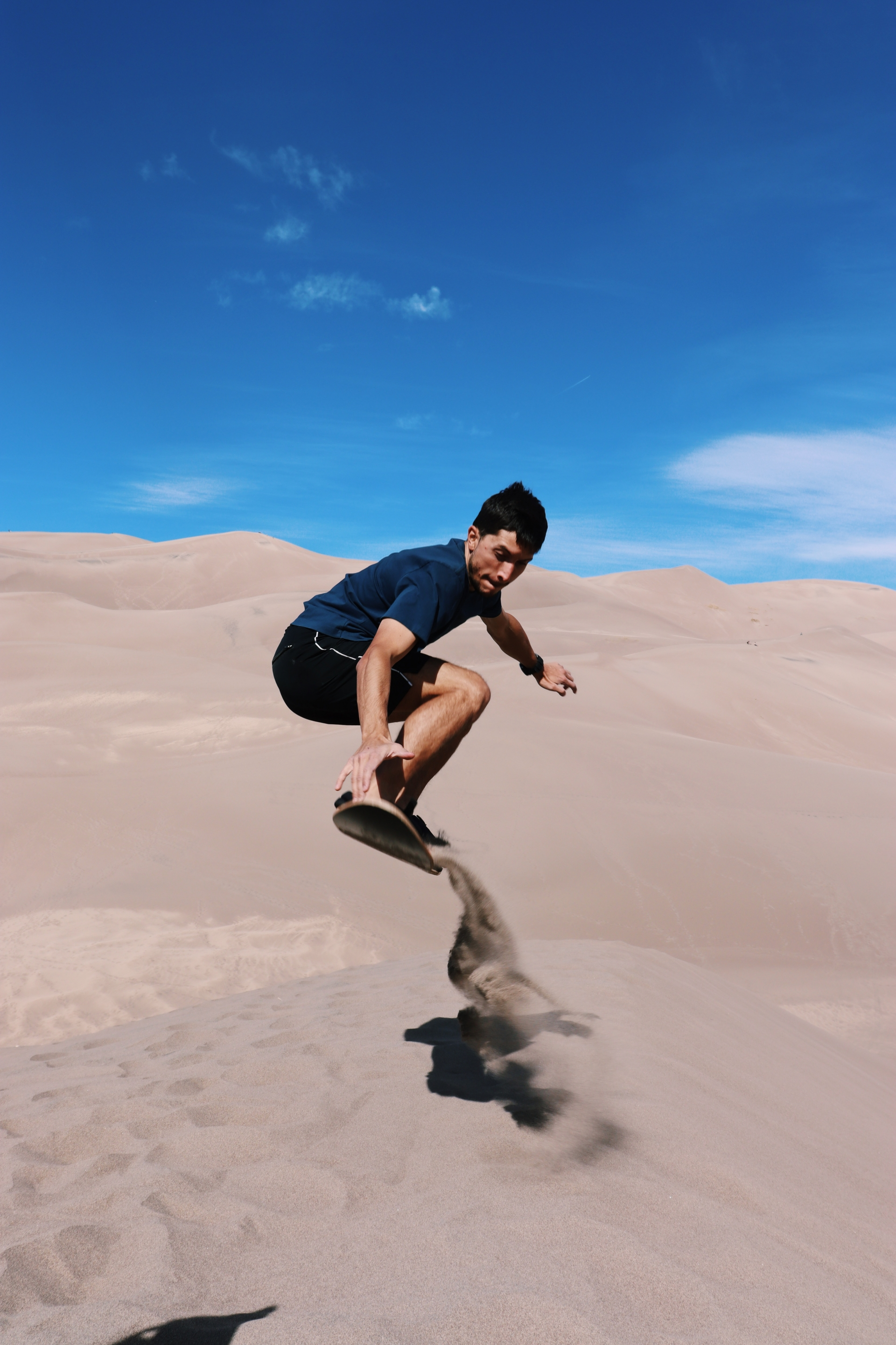 A young person sand boarding on a dune