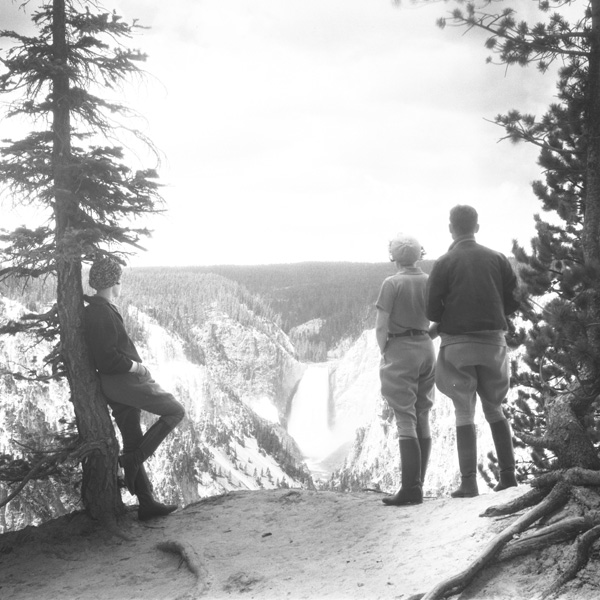 Three hikers look across a valley