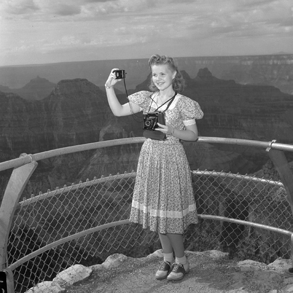 A girl takes a self portrait at a lookout point along the Grand Canyon
