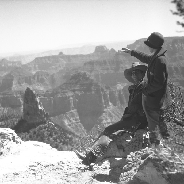 A woman points out features in the Grand Canyon landscape