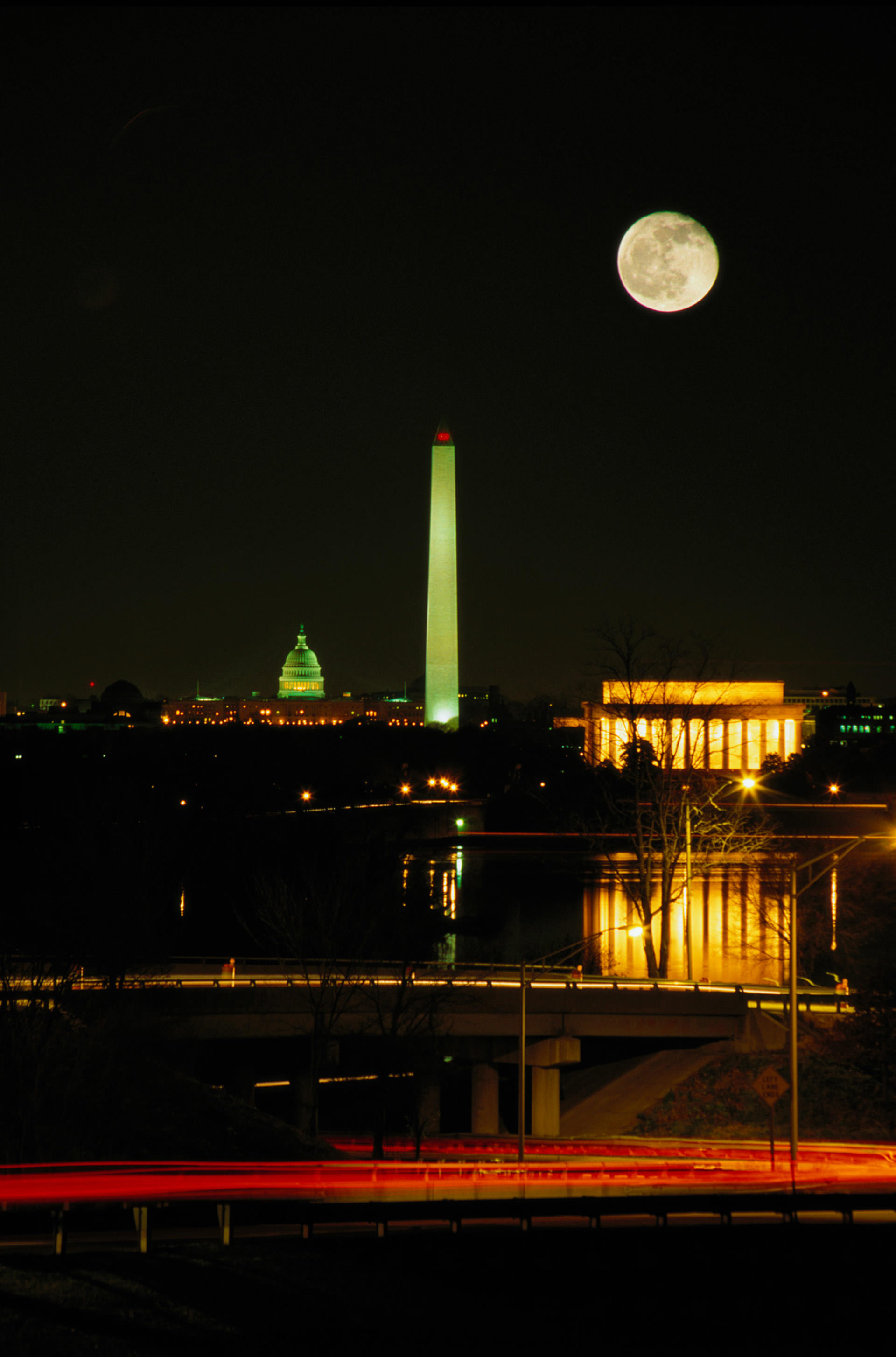 Nightime skyline view of Washington Monument and the moon